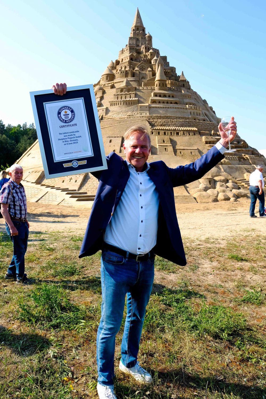Thomas van den Dungen vom Sandskulpturenfestival in Binz vor der höchsten Sandburg der Welt