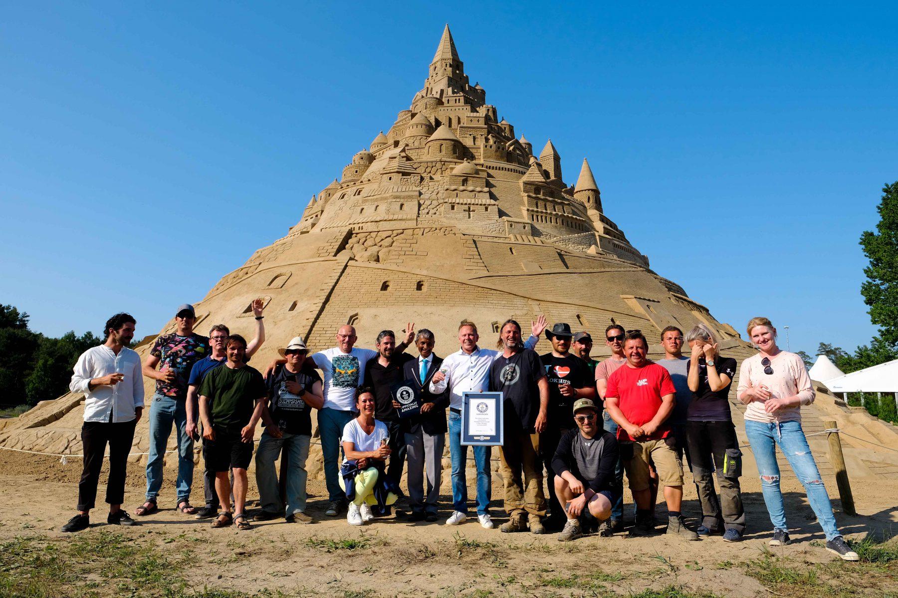 Das Team um Thomas van den Dungen vor der höchsten Sandburg der Welt